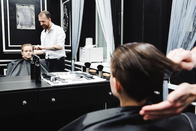 Молодой красивый парикмахер делает стрижку милый мальчик в парикмахерской