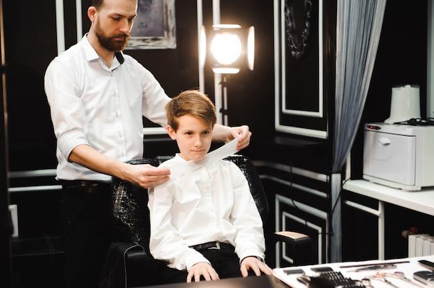 理髪店でかわいい男の子の散髪を作る若いハンサムな床屋。