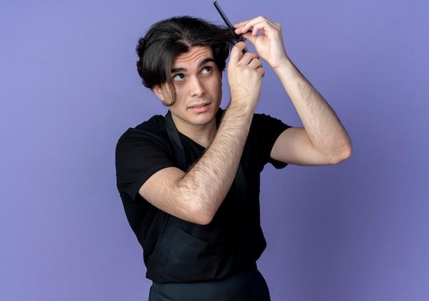 青で隔離の均一な櫛の髪の若いハンサムな理髪店の男