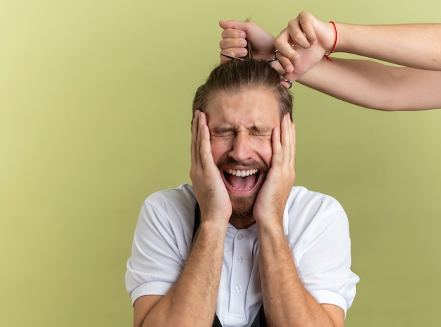 Young handsome barber putting hands on face with closed eyes scared about getting all his hair cut off isolated on olive green background with copy space