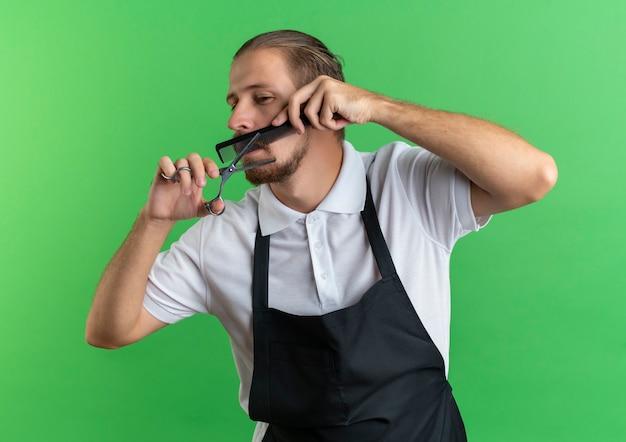 均一なコーミングを身に着けている若いハンサムな床屋は、緑の背景で隔離された側を見て彼の口ひげをカットします
