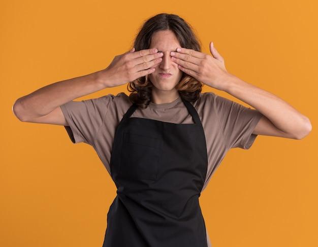 オレンジ色の壁に分離された手で目を覆う制服を着た若いハンサムな理髪師