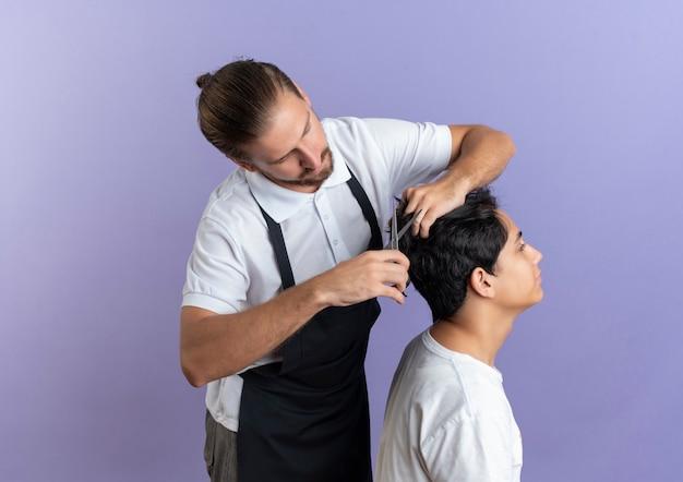 Молодой красивый парикмахер в униформе делает стрижку для молодого клиента, изолированного на фиолетовом фоне с копией пространства
