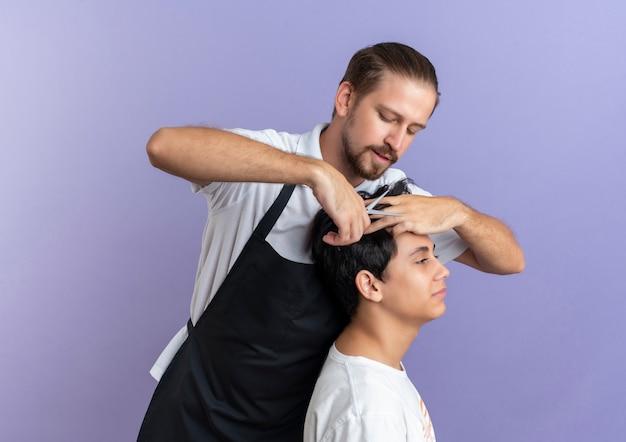 紫色の背景で隔離の若いクライアントのために散髪をしている制服を着ている若いハンサムな理髪店