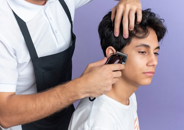 Young handsome barber wearing uniform doing haircut for young client isolated on purple background