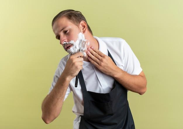 Giovane barbiere bello che indossa l'uniforme che rade la barba con il rasoio a mano libera e si tocca il collo guardando il lato isolato su sfondo verde oliva