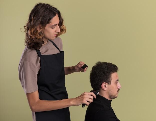 Giovane barbiere bello che indossa l'uniforme in piedi in vista di profilo facendo taglio di capelli per il suo giovane cliente