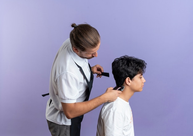 Young handsome barber wearing uniform standing in profile view doing haircut for young client isolated on purple background with copy space