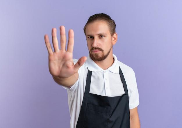 Giovane barbiere bello che indossa l'uniforme allungando la mano verso la telecamera gesticolando stop isolato su sfondo viola con spazio di copia