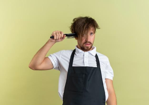 コームを保持し、コピースペースでオリーブグリーンの背景に分離された自殺を身振りで示す野生の髪を持つ若いハンサムな理髪師