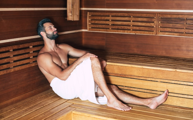 Young handsome beard man in the bath towel is relaxing in the hot sauna while vacation Premium Photo