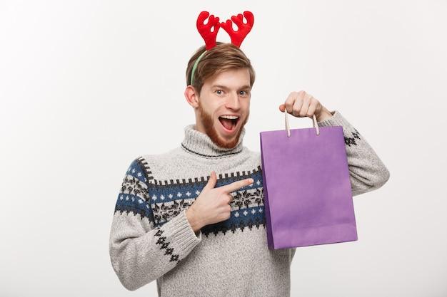 Giovane uomo bello della barba felice con il sacchetto della spesa nella mano isolata su bianco.
