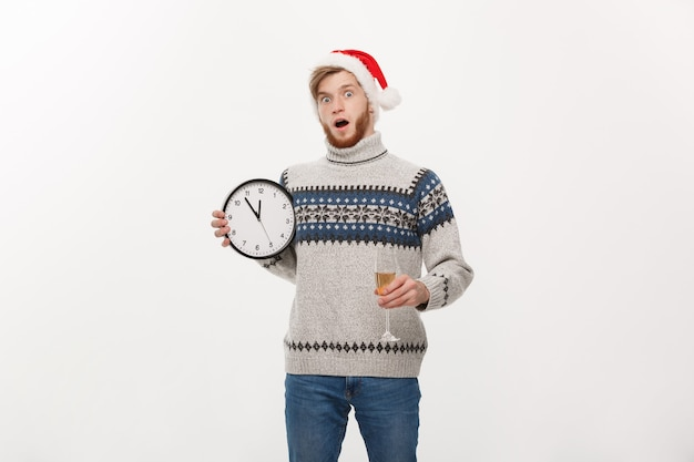 Giovane uomo bello con la barba in maglione con orologio bianco e champagne su bianco