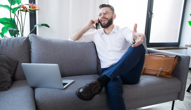 Молодой красивый бородатый деловой человек в очках и формальной смарт-одежде сидит на диване, расслабляясь и используя смартфон