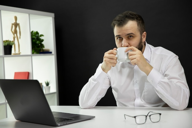 Young handsome bearded businessman in white shirt dreaming enjoying cup of cappuccino, male freelancer sitting at desk in front of laptop in home office. freelance, remote job, self employed concept