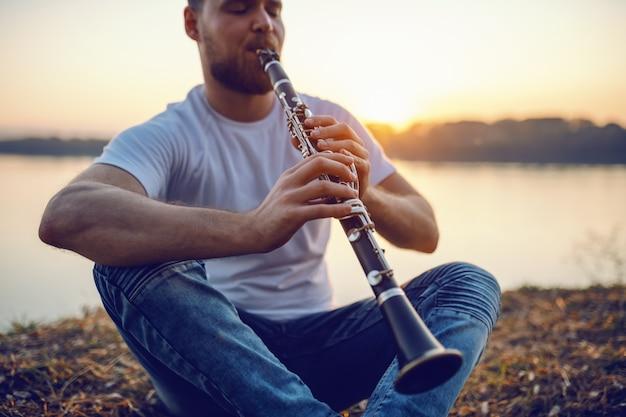 Молодой красивый бородатый кавказских белокурый человек сидит на скале и играет кларнет.
