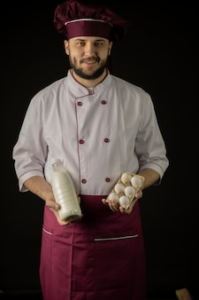 Young handsome bearded chef man in uniform holds bottle of milk and eggs