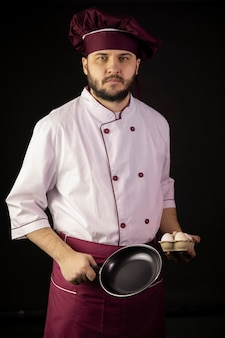 Young handsome bearded chef man in uniform holds frying pan and eggs