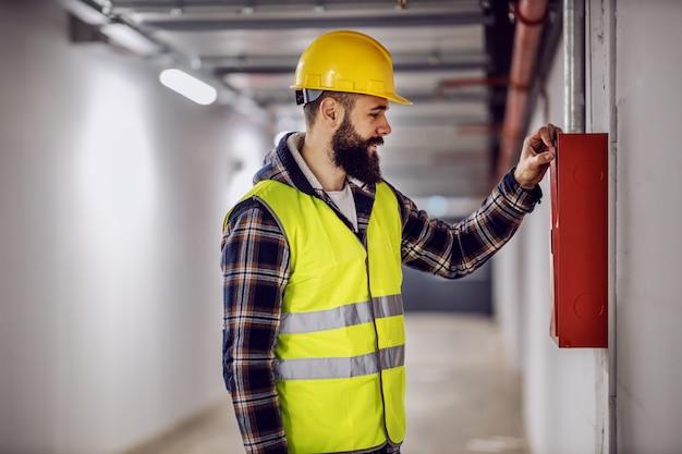 若いハンサムなひげを生やした電気技師再構築プロセスで建物に立って、配電ボックスをチェックアウト。