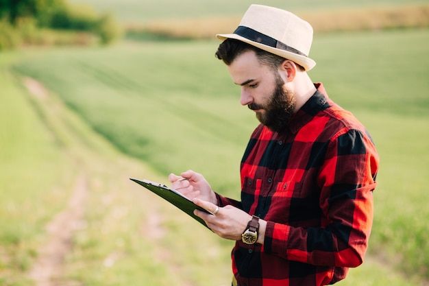 Young handsome bearded farmer with folder standing in green wheat field in early summer
