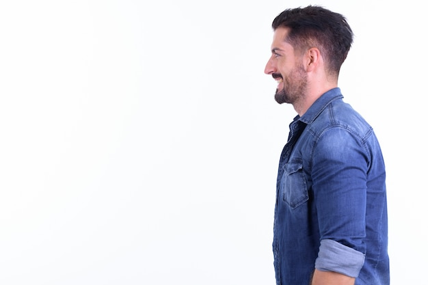 Young handsome bearded hipster man isolated against white wall