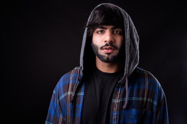 黒に対して若いハンサムなひげを生やしたインド人