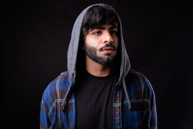 黒に対して若いハンサムなひげを生やしたインド人 Premium写真