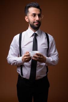 茶色の壁に対して若いハンサムなひげを生やしたイランの実業家
