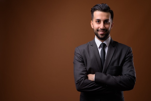 Young handsome bearded iranian businessman against brown wall