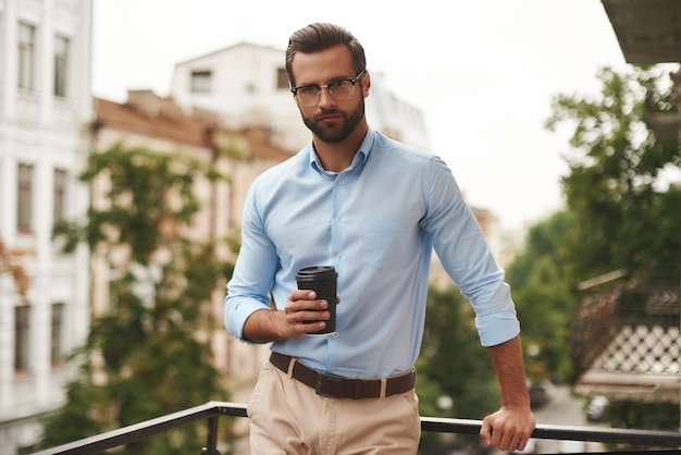Young and handsome bearded man in eyeglasses and formal wear holding cup of coffee and looking away