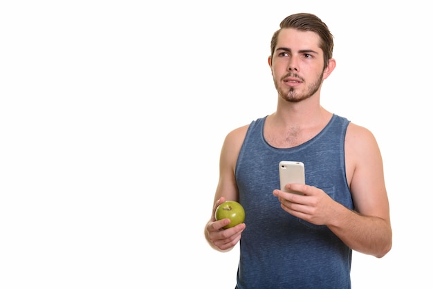 Young handsome bearded man holding apple and using phone ready for gym