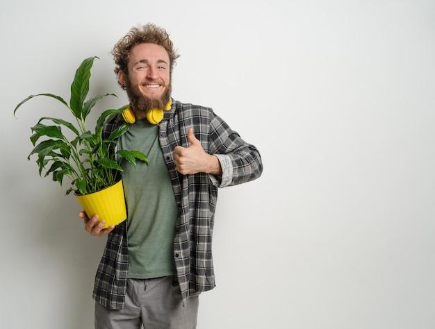 Молодой красивый бородатый мужчина держит желтый цветочный горшок с растением в клетчатой рубашке и желтых наушниках