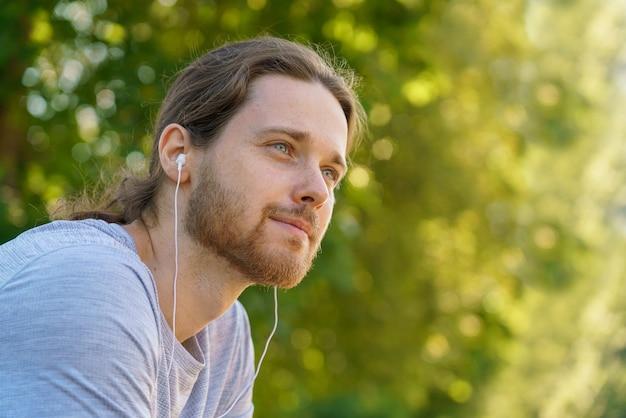 Молодой красивый бородатый мужчина в наушниках отдыхает после утренней спортивной тренировки