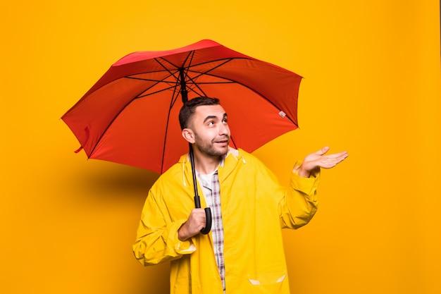 Молодой красивый бородатый мужчина в желтом плаще с красным зонтом пытается увидеть, не изолирован ли дождь на оранжевом фоне