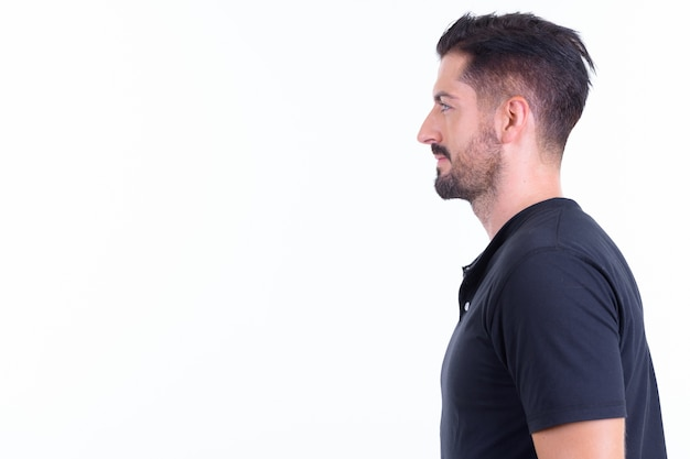 Young handsome bearded man isolated against white wall