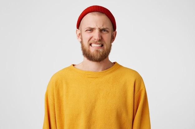 Молодой красивый бородатый мужчина изолирован над белой стеной с выражением отвращения