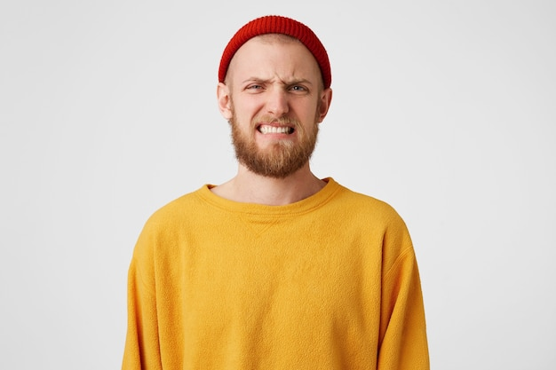 Young handsome bearded man isolated over white wall, with disgusted expression