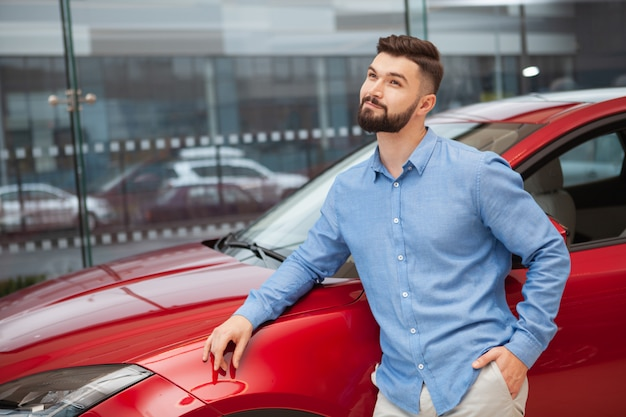 Young handsome bearded man leaning on a car at automobile dealership, looking away dreamily