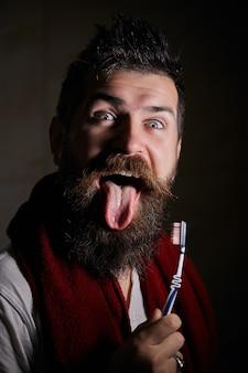 긴 수염과 찡그린 얼굴에 혀를 보여주는 콧수염 젊은 잘 생긴 수염 난된 남자 초상화. .