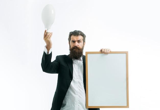 若いハンサムなひげを生やした男の科学者または白いアイデアコピースペースの概念で隔離の教師ボードを保持している教授