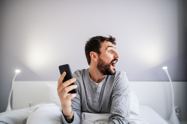 Young handsome bearded man sitting in the bed in bedroom and holding smart phone