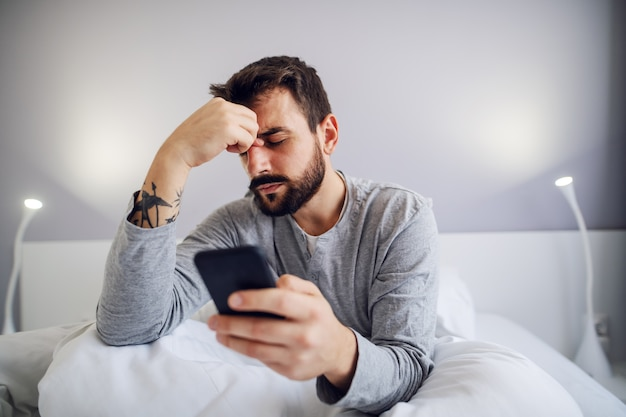 Young handsome bearded man sitting in bedroom, holding smart phone and getting nervous about message