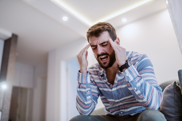 Young handsome bearded man sitting on sofa in living room, holding head and having headache.