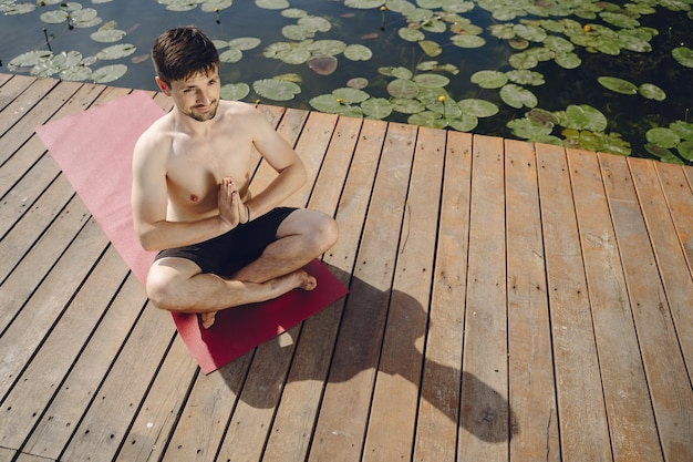 Young handsome bearded man sitting on wooden pier in summer day. meditating and relaxing.