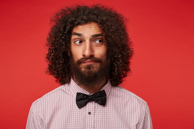 Молодой красивый бородатый мужчина с каштановыми кудрявыми волосами в клетчатой рубашке и черном галстуке-бабочке позирует, глядя в сторону с сомневающимся лицом и скрестив губы