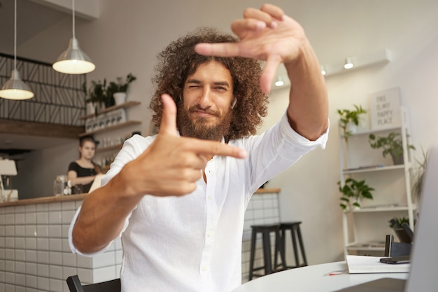 目を閉じて指を使用して焦点を当て、手でフレームジェスチャーを作成し、見たり笑ったり、巻き毛の茶色の髪を持つ若いハンサムなひげを生やした男