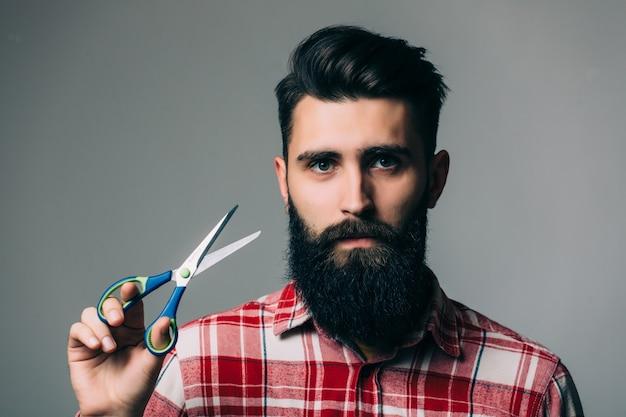 Giovane uomo barbuto bello con baffi barba lunga e capelli castani che tiene forbici parrucchiere o barbiere con faccia emotiva sul muro grigio