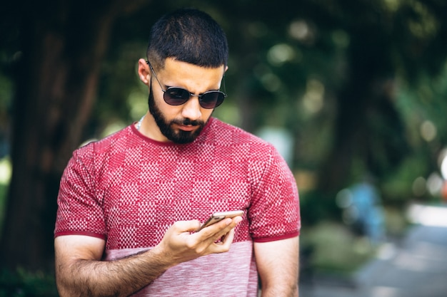 Young handsome bearded man with phone