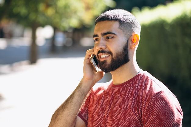 電話で若いハンサムなひげのある男