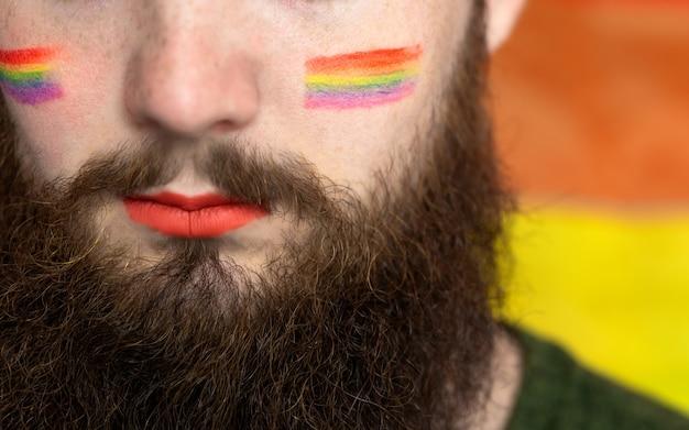 Молодой красивый бородатый мужчина с флагом гордости на щеке радужный флаг, стоящий за пол лгбтк